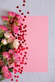 Plano de fundo dia dos namorados. rosas em rosa pastel e um coração de confete vermelho. conceito dia dos namorados