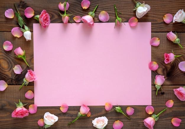 Plano de fundo dia dos namorados. teste padrão floral frame redondo feito de rosas cor de rosa e bege, folhas verdes sobre fundo de madeira.