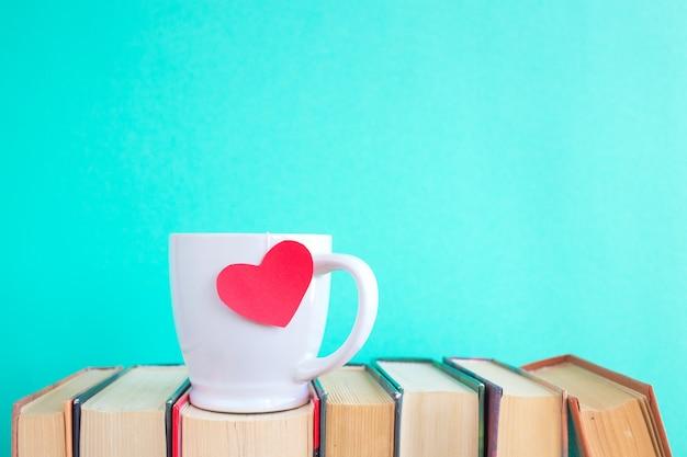 Plano de fundo dia dos namorados. xícara de café ou chá ou café sobre livros antigos