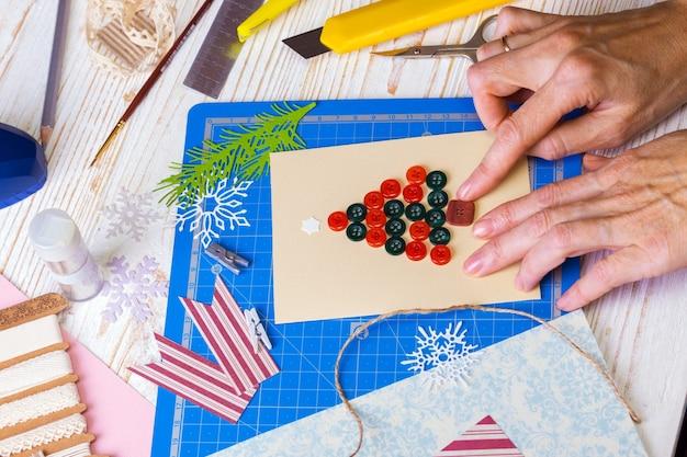 Plano de fundo do álbum de recortes. menina fazendo cartão de natal e ferramentas com decoração