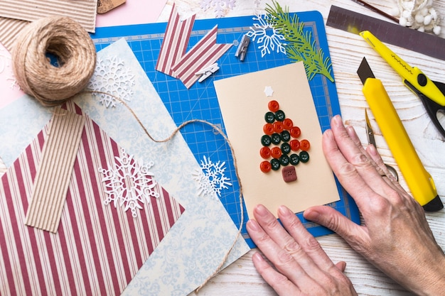 Plano de fundo do álbum de recortes. menina fazendo cartão postal de natal com botões e ferramentas com decoração