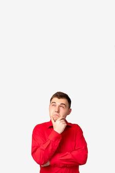 Plano de fundo do anúncio. oferta especial. homem duvidoso de camisa vermelha isolado, considerando a opção no espaço em branco da cópia.