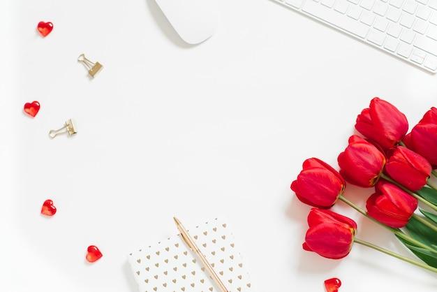Plano de fundo do dia dos namorados com teclado de computador, presente e vista superior da tulipa vermelha em branco cópia espaço