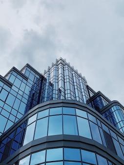 Plano de fundo do edifício de vidro da fachada em um céu azul