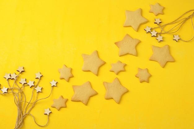 Plano de fundo do feriado - biscoitos de gengibre e estrelas - vista superior com espaço de cópia para o texto