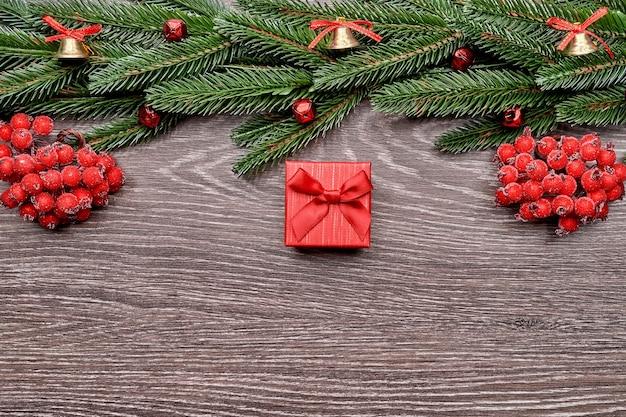 Plano de fundo do feriado com desejos de temporada e borda de galhos de árvore de natal de aparência realista decorados com frutas.
