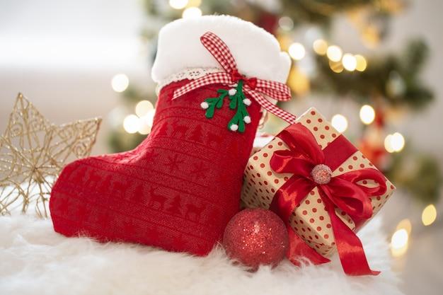 Plano de fundo do feriado de ano novo com uma meia decorativa e caixa de presente em um ambiente caseiro aconchegante close-up.