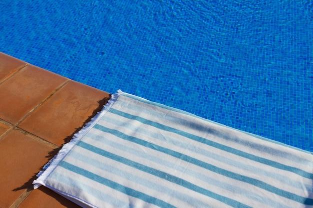 Plano de fundo do resort com toalha listrada perto da água azul clara da piscina