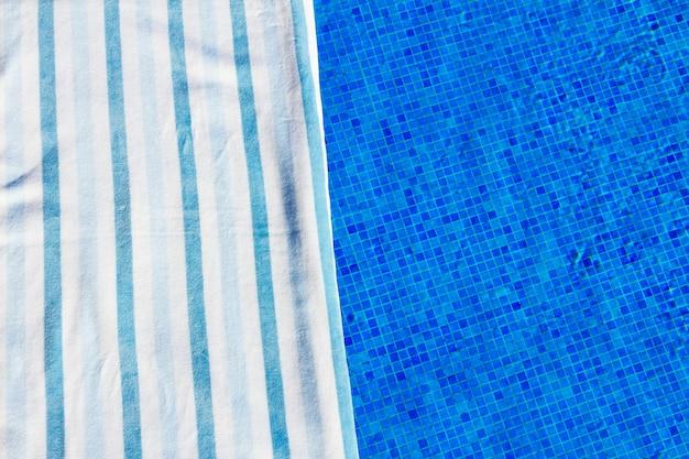 Plano de fundo do resort com toalha listrada perto da água da piscina