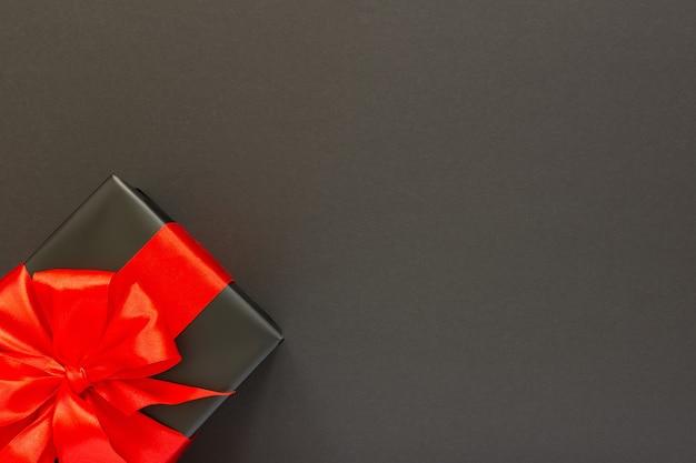 Plano de fundo festivo com presente, caixa de presente preta com fita vermelha e arco em fundo preto, conceito de sexta-feira preta, leiga plana, vista de cima