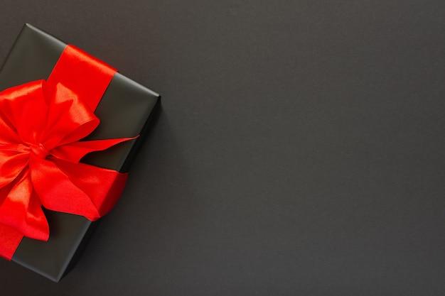 Plano de fundo festivo com presente, caixa de presente preta com fita vermelha e arco em fundo preto, conceito de sexta-feira preta, vista plana, vista de cima