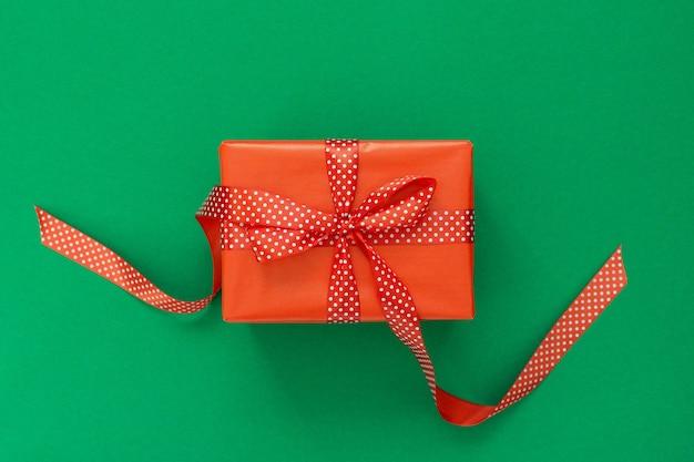 Plano de fundo festivo com presente, caixa de presente vermelha com fita em bolinhas e arco em fundo verde, disposição plana, vista de cima
