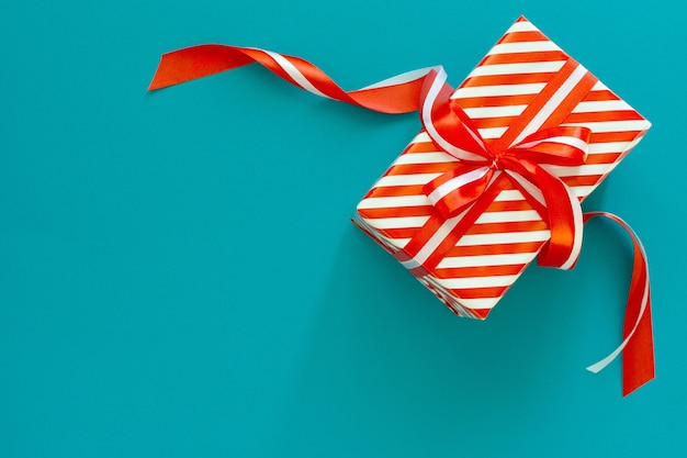 Plano de fundo festivo com presente listrado de vermelho e branco, caixa de presente com fita e arco em um fundo azul turquesa, vista plana, vista de cima