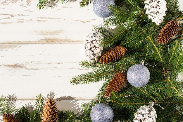 Plano de fundo festivo de ano novo com espaço para seu texto. ramos de abeto, cones de floresta e prata, bolas azuis cintilantes. fundo de madeira branco.