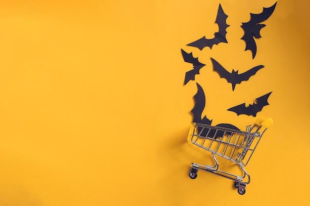 Plano de fundo festivo de halloween com morcegos de papel em um carrinho de compras. faça a maquete categoricamente para festa ou venda. vista superior. copiar espaço