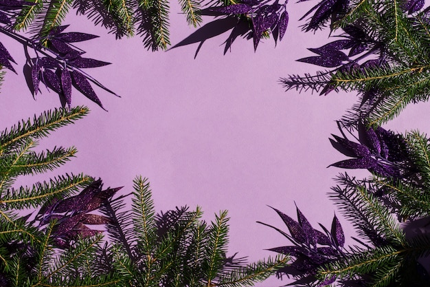 Plano de fundo festivo ou de ano novo com elementos decorativos de ramos de abeto e folhas decorativas lilás com lantejoulas. uma cópia do espaço.