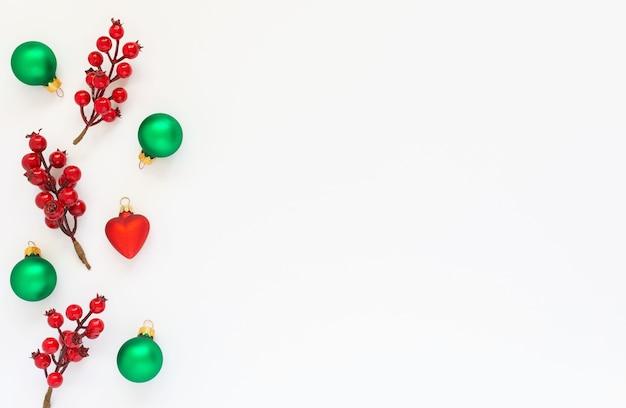 Plano de fundo festivo, ramo de espinheiro e bolas de árvore de natal em um fundo branco, vista de cima plana, cópia espaço