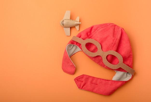 Plano de fundo infantil, chapéu de piloto, avião de brinquedo de madeira, fundo laranja, vista superior