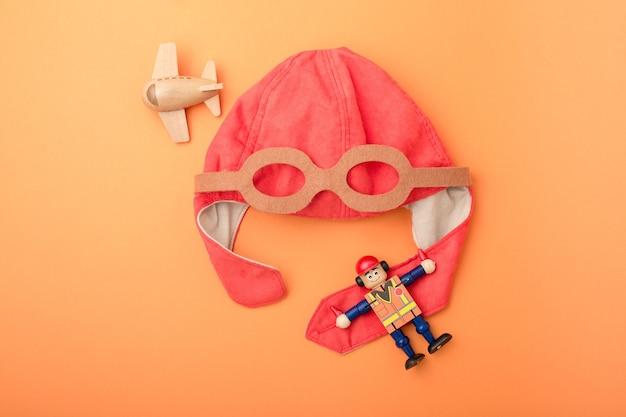 Plano de fundo infantil, chapéu de piloto, avião de madeira de brinquedo e homem, fundo laranja, vista superior