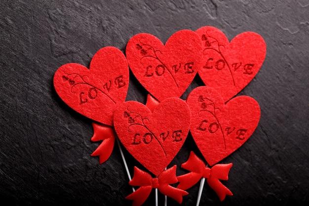 Plano de fundo lindo dia dos namorados com corações vermelhos em fundo preto. cartão de dia dos namorados. conceito de amor.