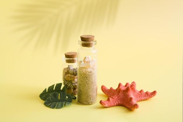 Plano de fundo minimalista de verão com mini garrafas e pequenas conchas, estrela do mar e folhas tropicais na superfície amarela