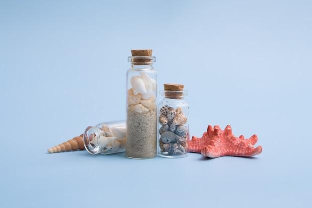 Plano de fundo minimalista de verão com mini garrafas, pequenas, conchas, areia, estrela do mar