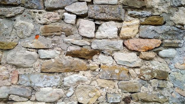 Plano de fundo na forma de uma parede de pedra ou blocos Foto Premium