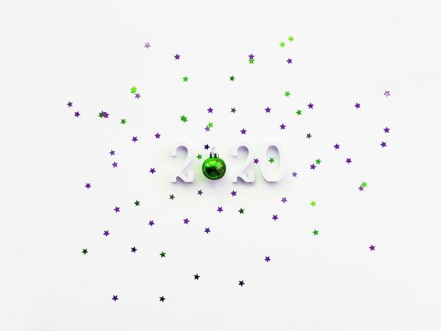 Plano de fundo natal e ano novo 2020 com números, bola verde brilhante e confetes estrela violeta.