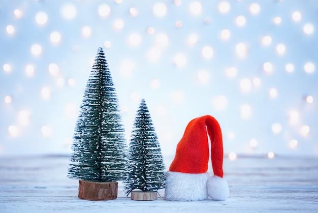 Plano de fundo natal e ano novo com chapéu de papai noel e árvores de natal. cartão de férias.