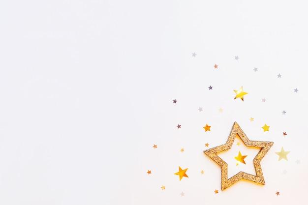 Plano de fundo natal e ano novo com estrela dourada cintilante e confetes.