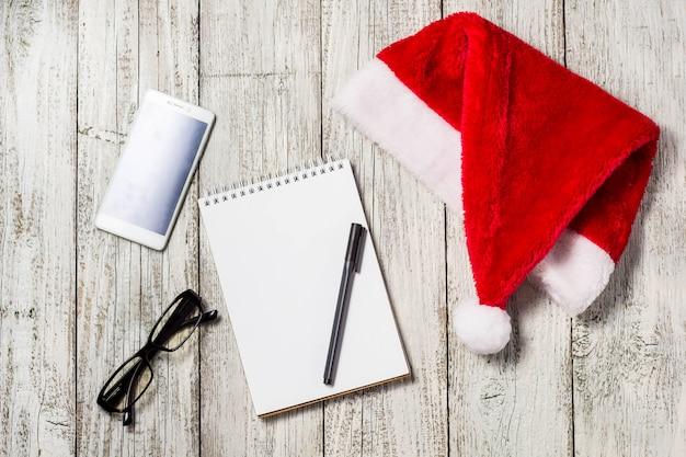 Plano de fundo natal e ano novo com smartphone, chapéu de papai noel vermelho, óculos, bloco de notas e caneta para seus desejos