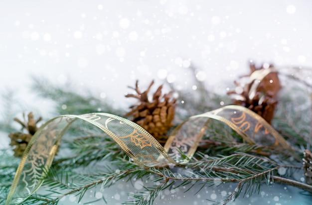 Plano de fundo natal e ano novo. ramos de abeto e cones, fita de presente.