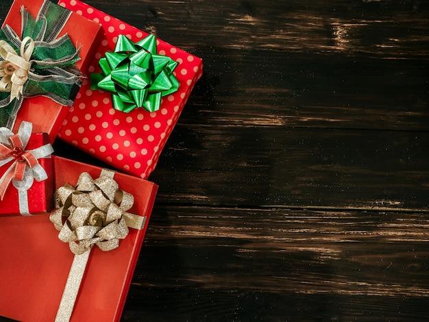 Plano de fundo natal e feliz ano novo. vista superior da bela caixa de presente vermelha com enfeites de arco verde e dourado brilhante em prancha de madeira escura