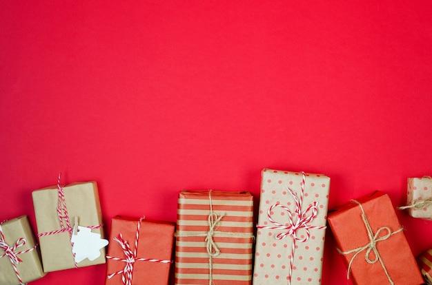 Plano de fundo natal ou ano novo, presentes embrulhados em papel ofício e fundo vermelho accessorieson, conceito de férias. camada plana, vista de cima, espaço de cópia, modelo de design de texto de cartão de saudação