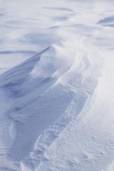 Plano de fundo nevado, superfície da terra coberta de neve após uma nevasca pela manhã sob o sol com camadas distintas de neve