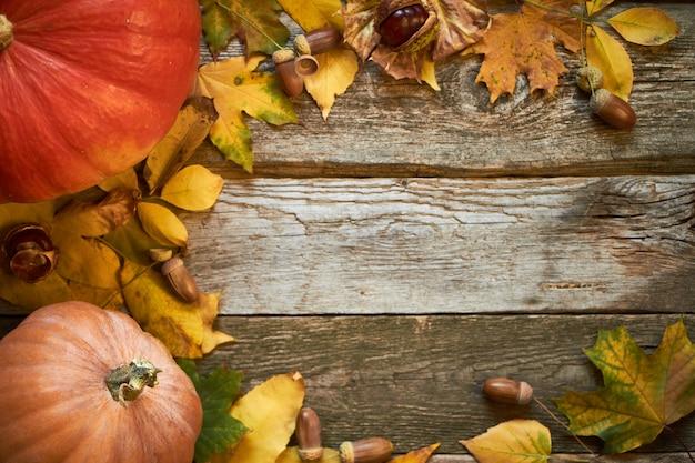 Plano de fundo outono de ação de graças em uma superfície de madeira escura, abóboras, folhas murchas, bolotas e castanhas