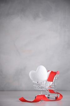 Plano de fundo para o cartão de dia dos namorados. conceito de dia dos namorados. coração em um carrinho de compras.