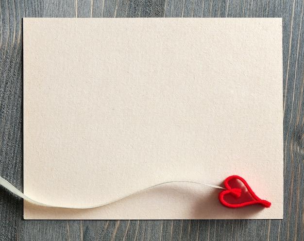 Plano de fundo para o desenho com uma folha de papel para anotações e um coração decorativo vermelho