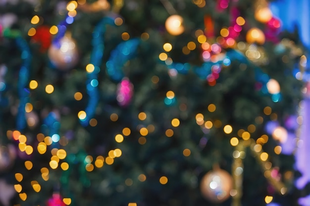 Plano de fundo para o designer. luzes coloridas turva em uma árvore de natal.