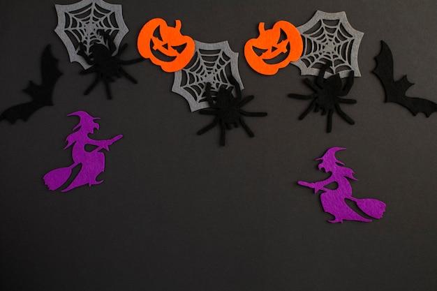 Plano de fundo para o halloween. aranhas decorativas, abóboras, teias de aranha e morcegos no fundo preto. copie o espaço. vista do topo.