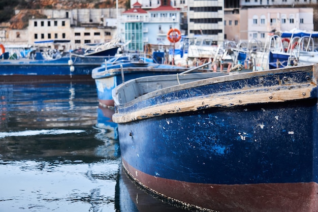 Plano de fundo - pequenos barcos de pesca azuis parcialmente desfocados no porto