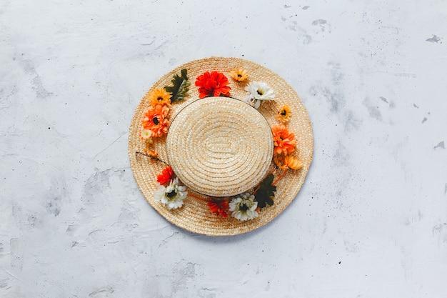 Plano de fundo plano de concreto cinza com flores coloridas de outono no chapéu de palha