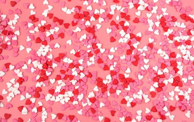 Plano de fundo romântico com pequenos corações em fundo rosa. a vista do topo. conceito 14 de fevereiro.
