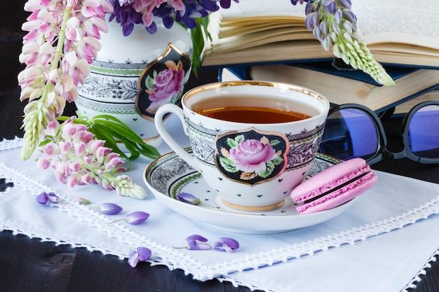 Plano de fundo romântico com uma xícara de flores de chá e livro aberto sobre a mesa branca