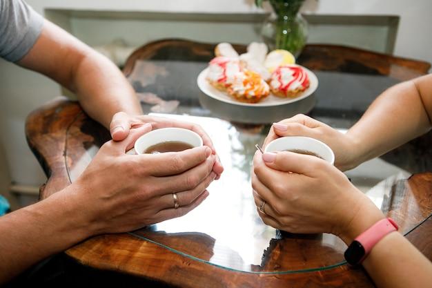 Plano de fundo romântico, duas xícaras de café e as mãos do casal apaixonado num encontro. jantar romântico no dia dos namorados