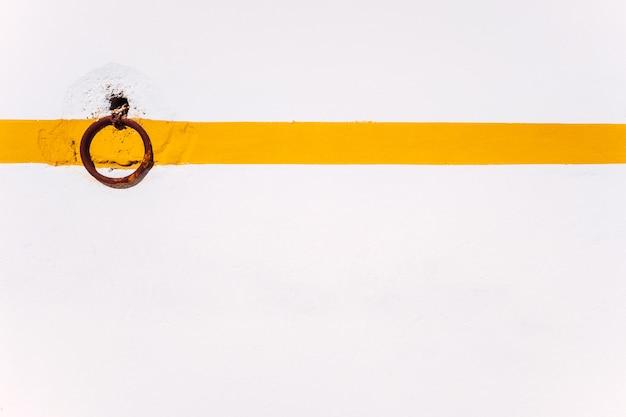 Plano de fundo rural de um anel enferrujado em uma parede branca com linha laranja para amarrar animais.