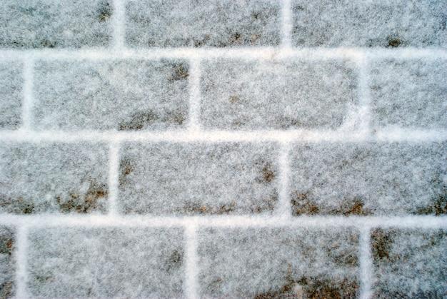 Plano de fundo, textura - ladrilhos de pavimento de granito coberto de neve