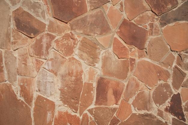 Plano de fundo texturizado com partículas de tijolo uma parede de pedaços de materiais parede com rachaduras e costuras