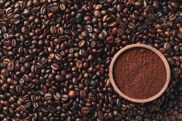 Plano de fundo texturizado de grãos de café com uma tigela de pó, close-up