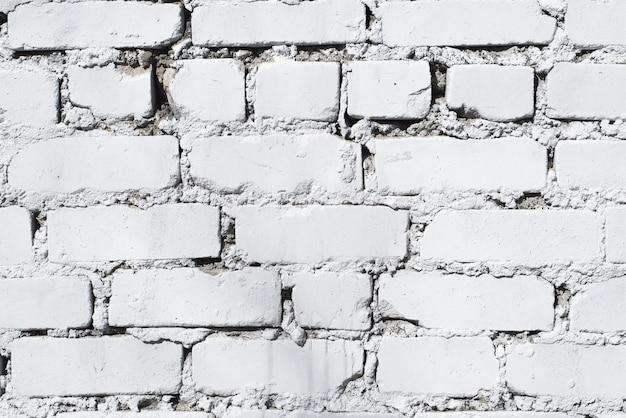 Plano de fundo texturizado de uma parede de tijolos pintada com tinta branca, close-up. pano de fundo